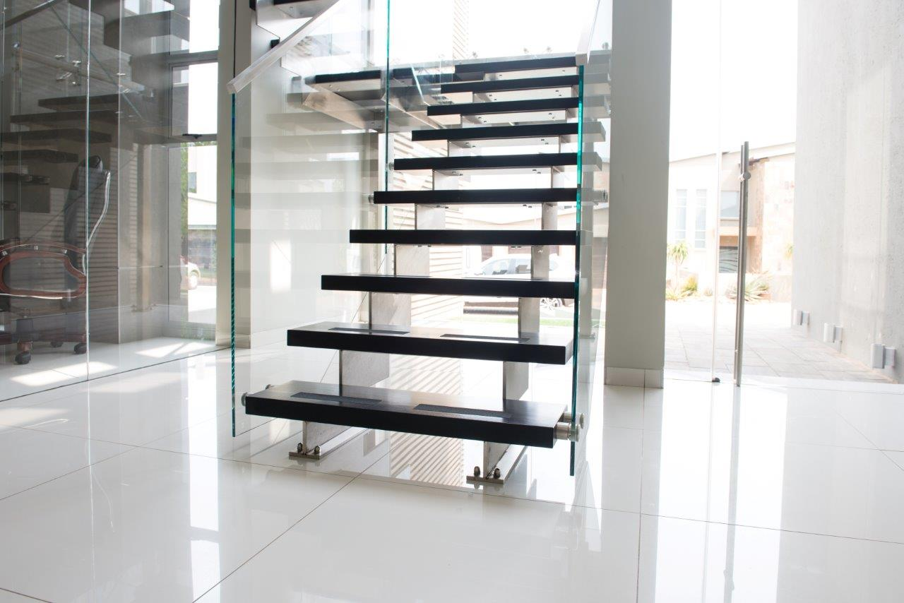black residential staircase with glass balustrades manufactured and installed by steel studio